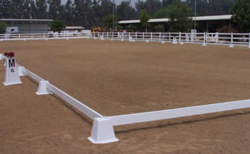 A dirt stable with a minor white fence.